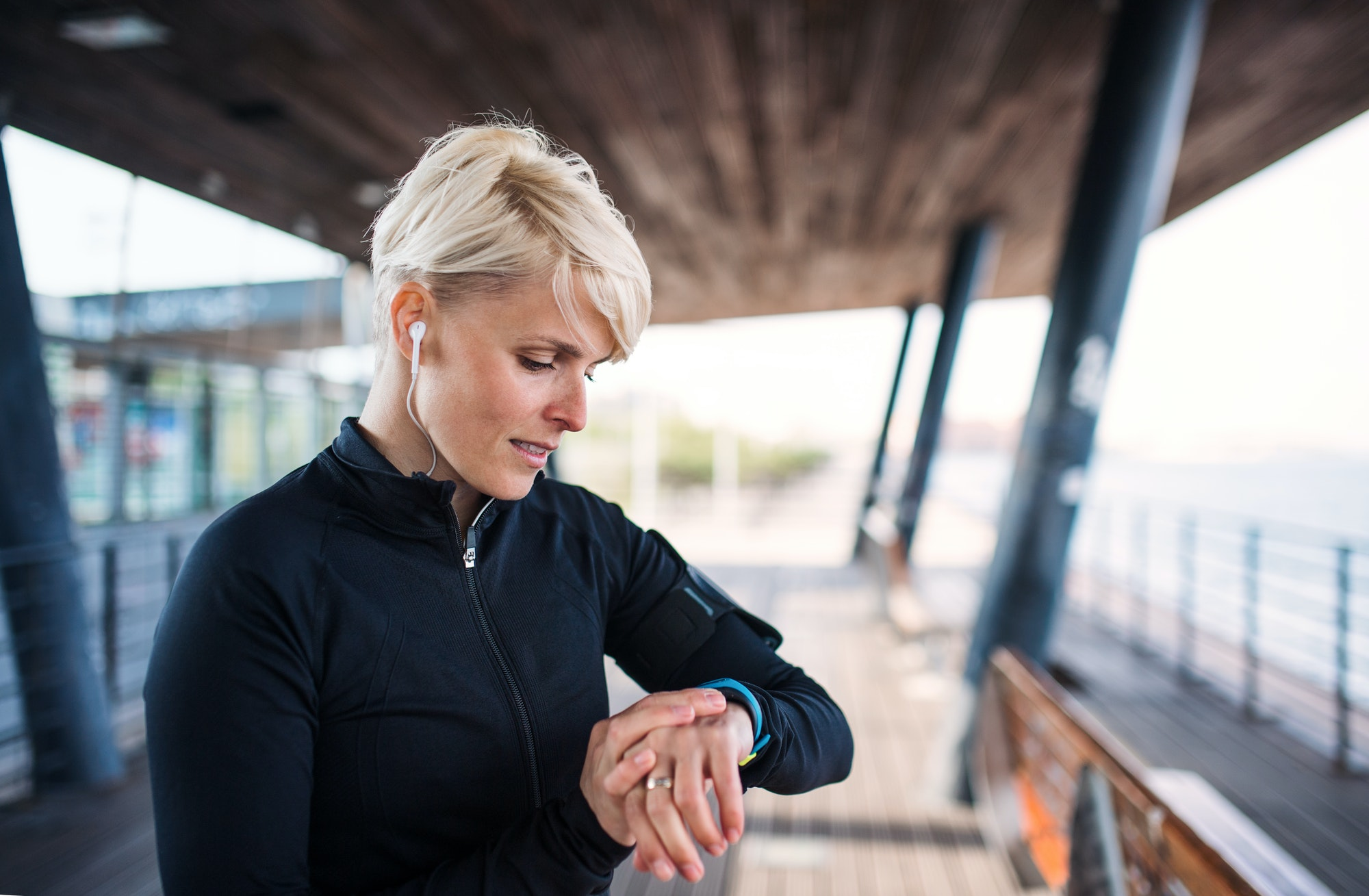 A portrait of young sportswoman with smartwatch outdoors, self-tracking.