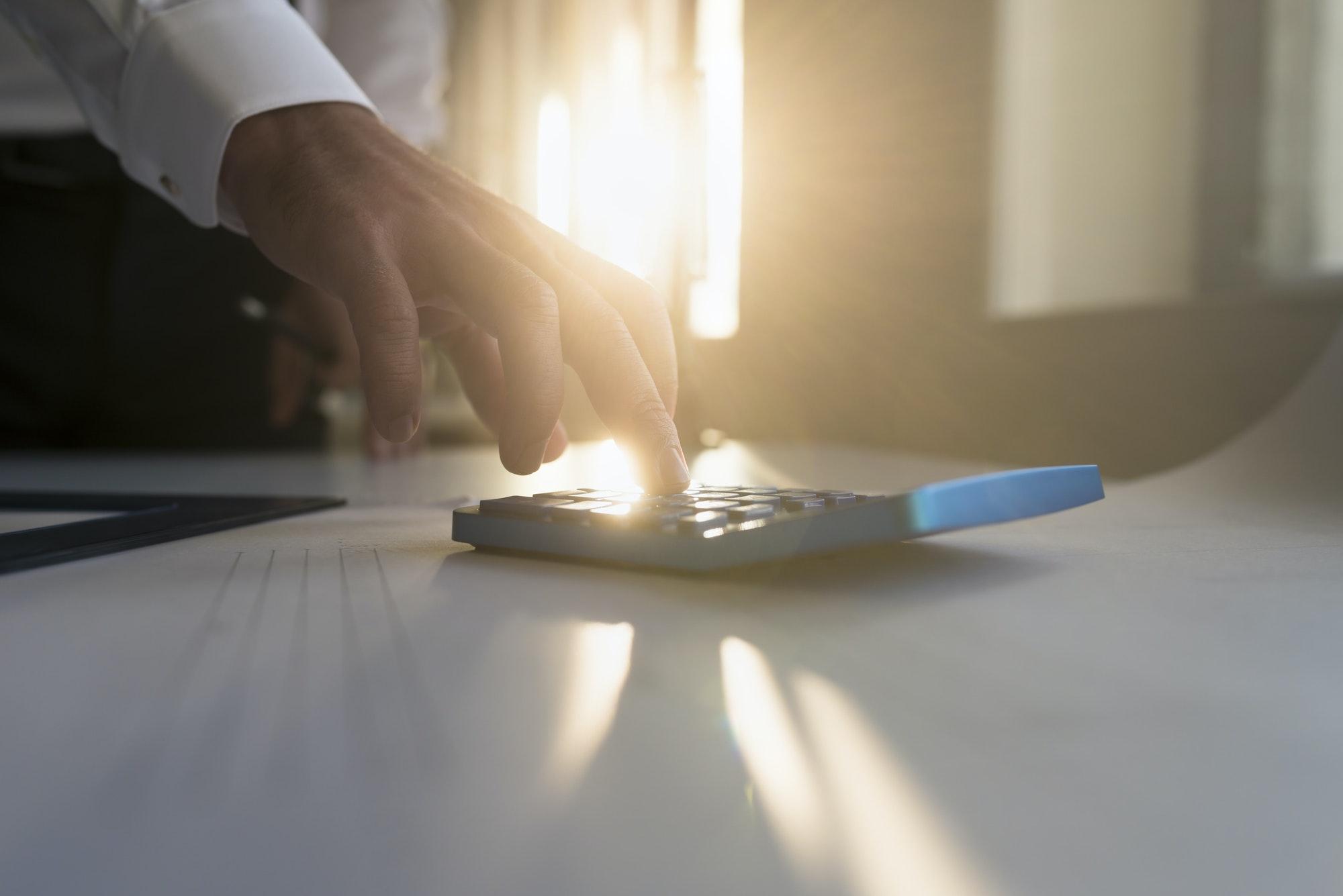 Hand of a businessman using a desk calculator