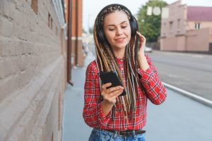 Young woman with colored pigtails listening to music in headphones on the street