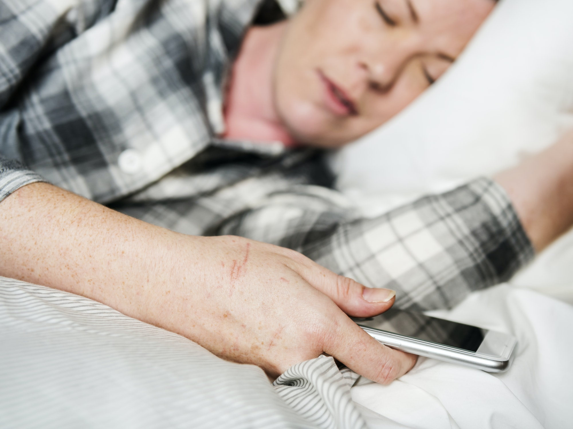 A woman sleeping in bed while carrying a phone