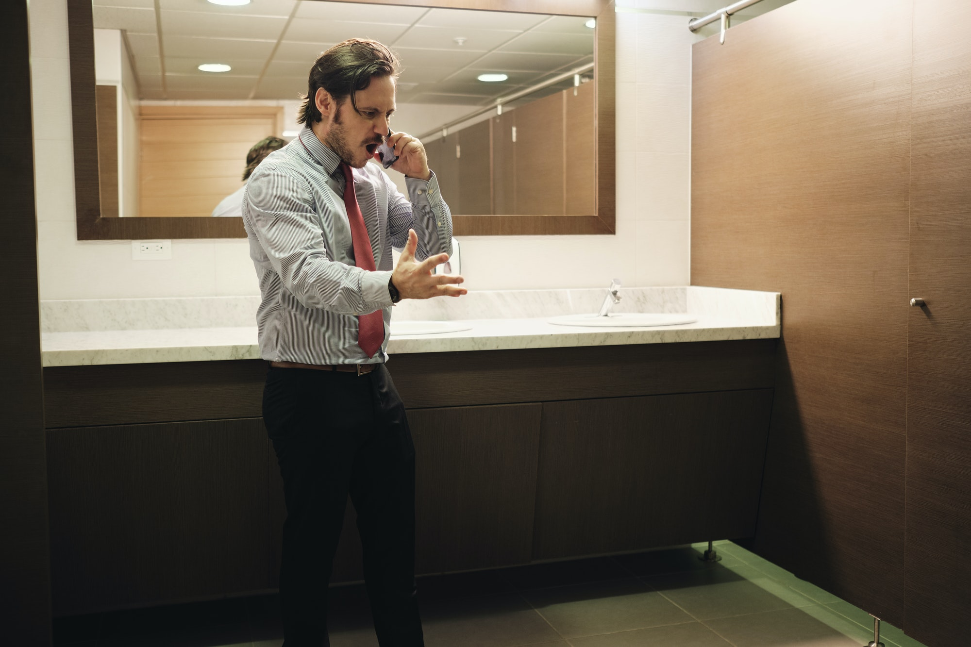 Furious Business Man Screaming On Cell Phone In Office Restroom