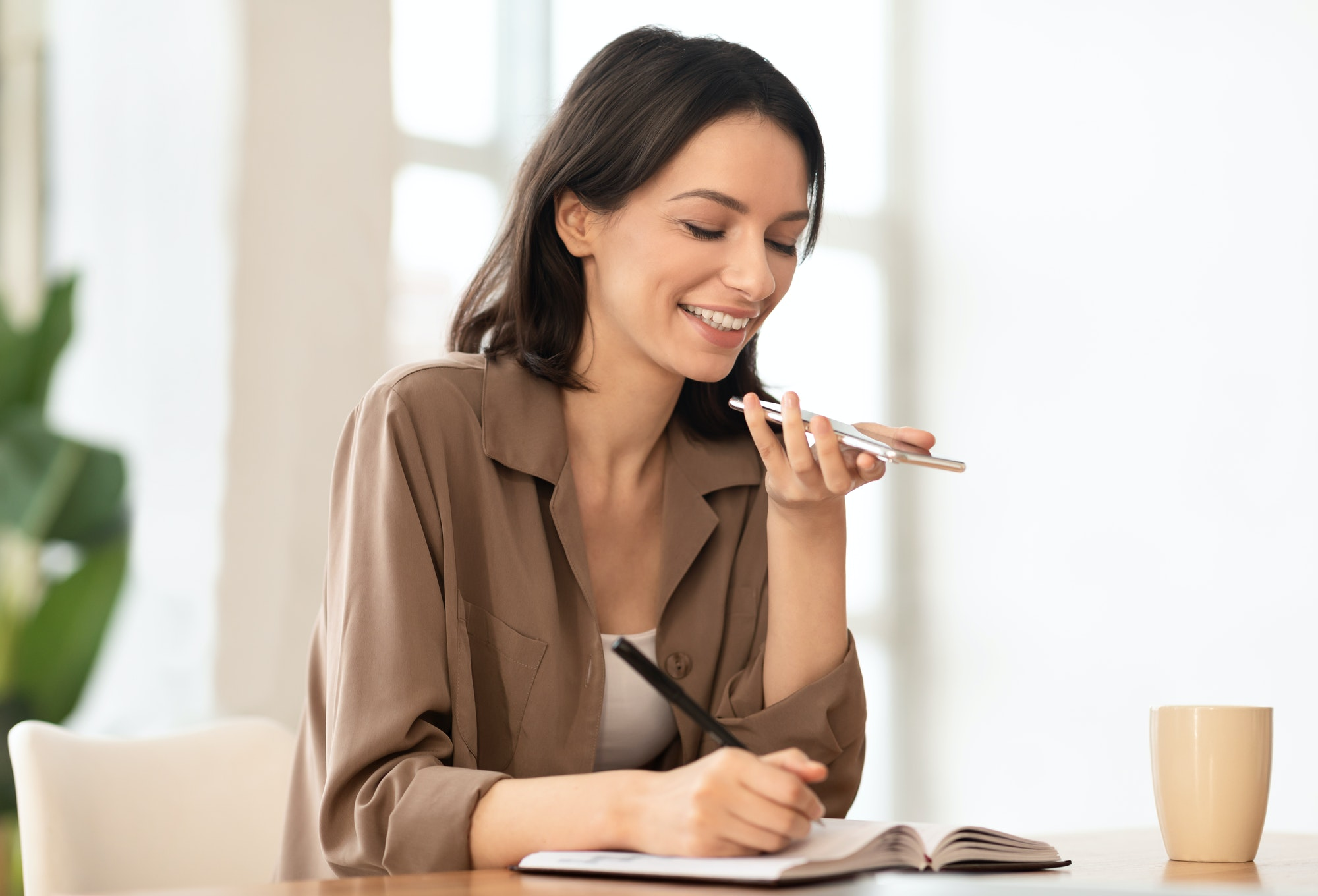 Woman using mobile voice recognition function and writing