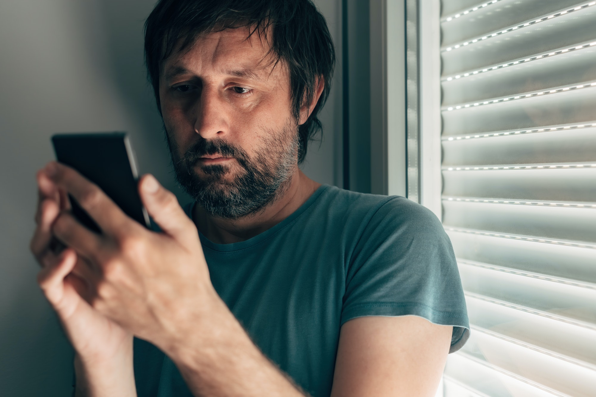 Man text messaging on mobile phone in privacy of bedroom